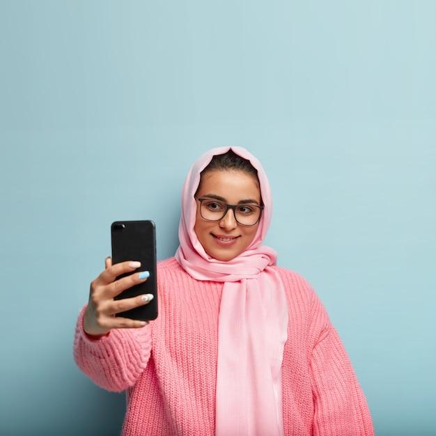 Gut aussehendes mädchen mit sanftem lächeln, schaut gerne auf den bildschirm des geräts, trägt eine rechteckige brille, einen seidenschleier, streckt die hand aus, um einen schönen schuss zu machen, hat maniküre, trägt einen rosa pullover, ist auf blau isoliert Kostenlose Fotos