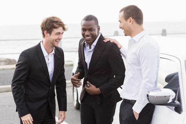 Gut gekleidete leute posieren neben einer limousine Premium Fotos