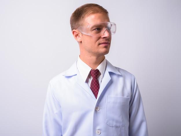 Gutaussehender arzt als wissenschaftler, der eine schutzbrille gegen leerraum trägt Premium Fotos