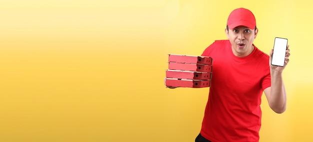 Gutaussehender asiatischer mann in der roten kappe, die italienische pizza der lebensmittelbestellung in pappkartons lokalisiert hält, die handy mit leerem weißem leerem bildschirm hält. Premium Fotos