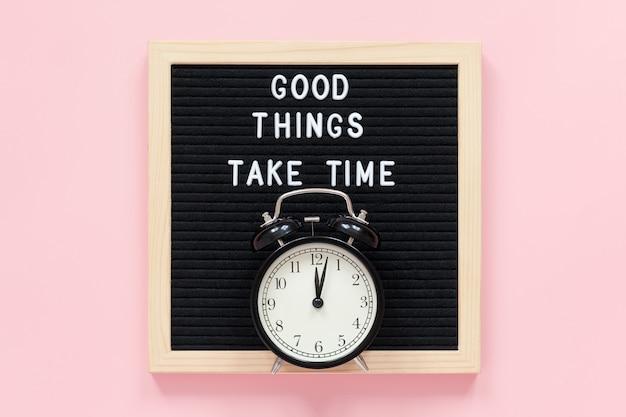 Gute dinge brauchen zeit. motivationszitat auf schwarzem briefbrett, schwarzer wecker auf rosa hintergrund. inspirierendes zitat des konzepts Premium Fotos