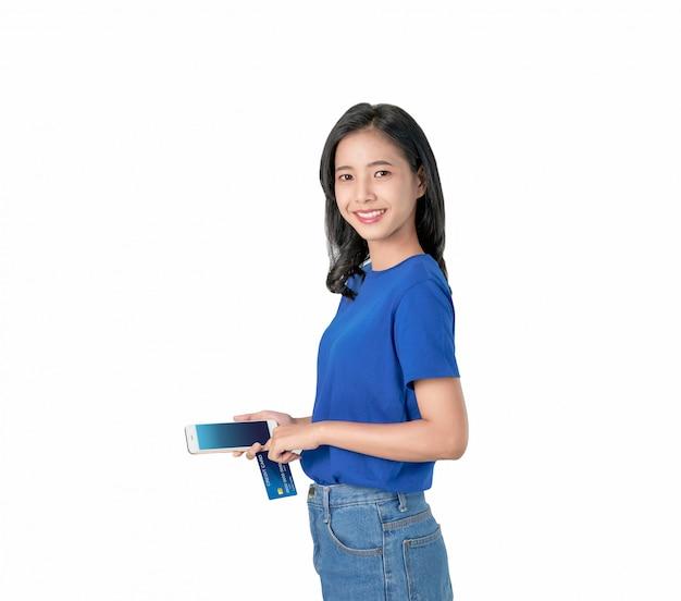 Gute haut der asiatin, die den smartphone und kreditkarte online kaufen mit dem hellen lächeln hält. Premium Fotos