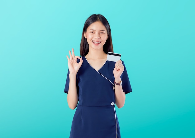 Gute haut der schönen asiatin, zeigt okayzeichen mit tragendem kleid und dem halten der kreditkartezahlung auf blauem hintergrund. Premium Fotos