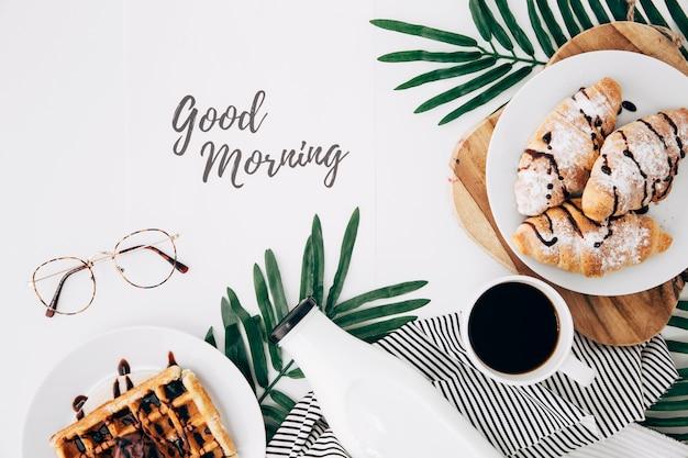 Guten morgen text mit brille; frisch gebackenes croissant; waffeln; flasche und kaffeetasse auf weißem schreibtisch Kostenlose Fotos