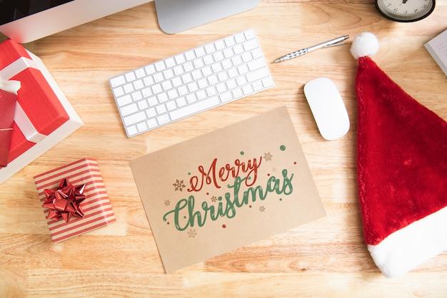 Guten rutsch ins neue jahr-feiertagsgrußpapierkartendesignmodell mit dekoration auf hölzerner tabelle. Premium Fotos