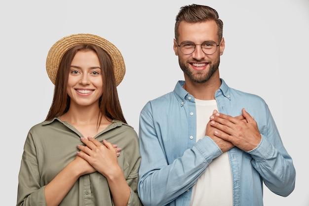 Gutherziges schönes paar, das gegen die weiße wand aufwirft Kostenlose Fotos