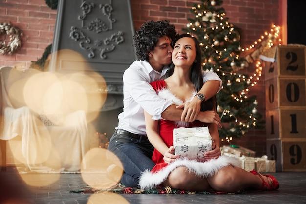 Guy gibt einen kuss für seine frau. schöne paare, die neues jahr im verzierten raum mit weihnachtsbaum und kamin hinten feiern Premium Fotos