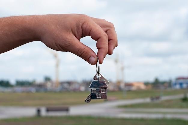Guy hält die schlüssel zum haus in seinen händen Premium Fotos