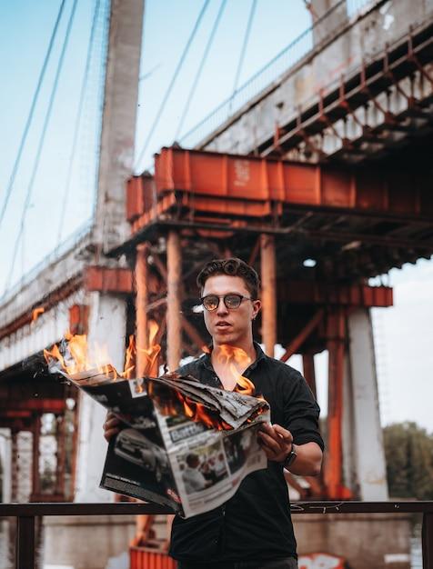 Guy liest eine brennende zeitung vor einer brücke Kostenlose Fotos