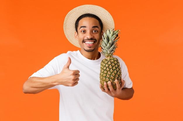 Guy reise genießen, empfehlen reisebüro. froher lächelnder hübscher junger mann des afroamerikaners, der thumbs-up zeigt, ananas hält und im urlaub, orange lächelt und sich entspannt Premium Fotos