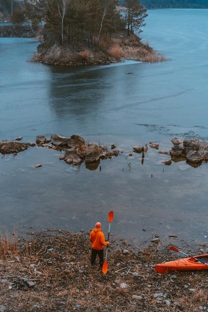 Guy steht mit einem ruder am zugefrorenen see Kostenlose Fotos