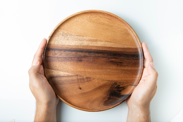 H, das leere hölzerne platte lokalisiert auf weißer, draufsicht hält. Premium Fotos