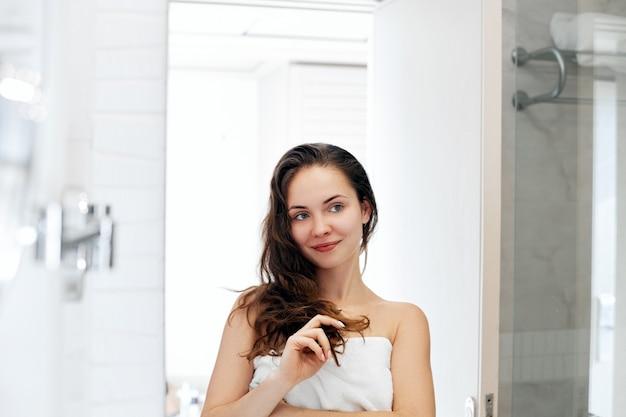 Haar- und körperpflege. frau, die haare berührt und lächelt, während sie in den spiegel schaut. porträt des glücklichen mädchens mit nassem haar im badezimmer, das conditioner und öl anwendet. mädchen verwendet schutz feuchtigkeitscreme Premium Fotos