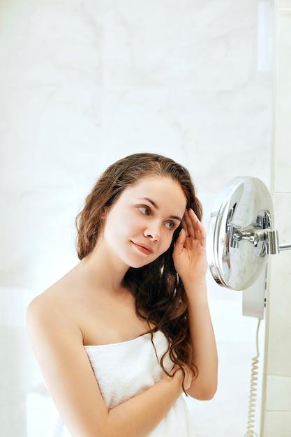 Haar- und körperpflege. frau, die haare berührt und lächelt, während sie in den spiegel schaut. porträt des glücklichen mädchens mit nassem haar im badezimmer, das conditioner und öl anwendet. Premium Fotos