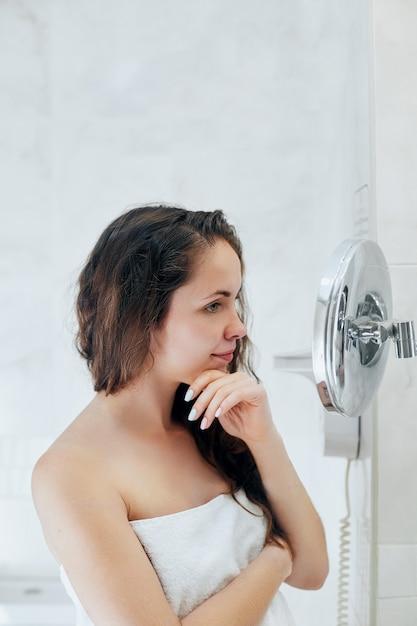 Haar- und körperpflege. frau, die nasses haar berührt und lächelt, während sie in den spiegel schaut. porträt des mädchens im badezimmer, das conditioner und öl anwendet. porträt der frau verwendet schutzfeuchtigkeitscreme. Premium Fotos