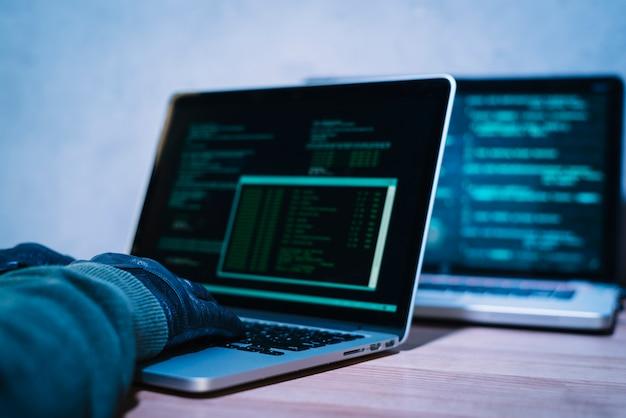 Hacker, der auf laptop schreibt Kostenlose Fotos