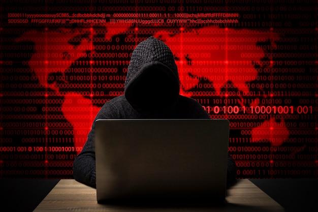 Hacker in einer jacke mit kapuze und laptop sitzt am tisch. symbole für identitätsdiebstahl, kontodiebstahl, bankdatendiebstahl und weltkarte hinzugefügt Premium Fotos