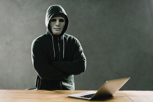 Hacker mit laptop auf dem tisch Kostenlose Fotos