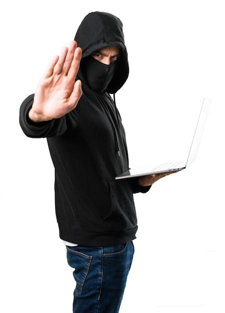 Hacker mit seinem computer, der stoppschild auf lokalisiertem weißem hintergrund macht Premium Fotos