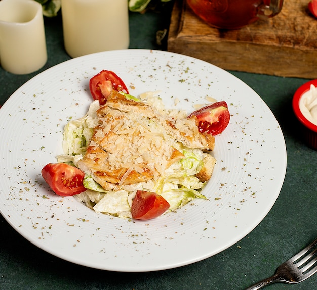 Hähnchen-caesar-salat mit gehacktem parmesan, salat und tomaten Kostenlose Fotos