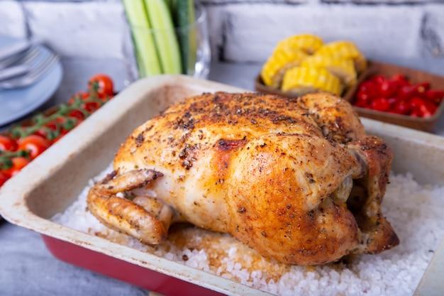 Hähnchen ganz auf salz gebacken. mit maiskolben, kirschtomaten, gurken und jalapenopfeffer. Premium Fotos