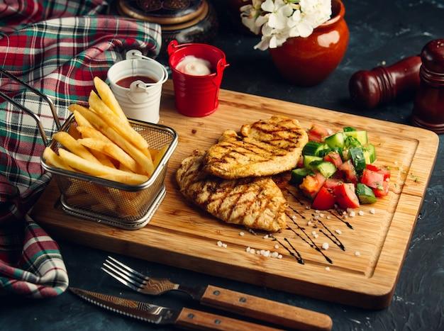 Hähnchenfiletsteak mit pommes und gemüsesalat. Kostenlose Fotos