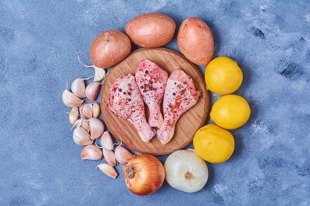 Hähnchenschenkel mit gemüse auf einem holzbrett auf blau Kostenlose Fotos