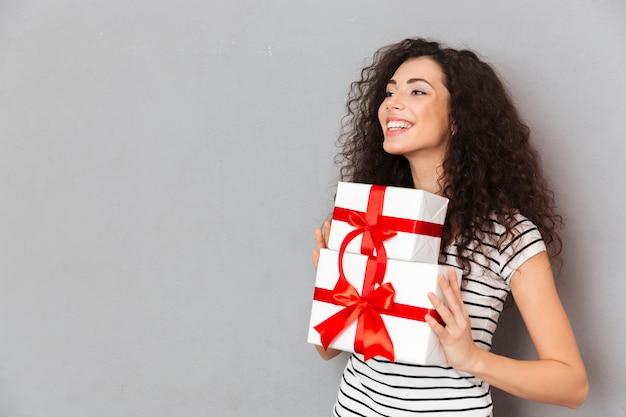 Hälfte drehte sich foto der herrlichen frau in dem gestreiften t-shirt, das zwei geschenk eingewickelte kästen mit den roten bögen hält, die über grauer wand aufgeregt und fröhlich sind Kostenlose Fotos