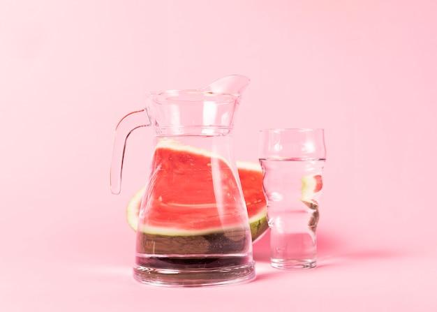 Hälfte geschnittene wassermelone mit wasserbehältern Kostenlose Fotos