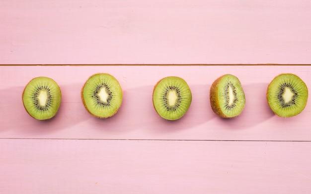 Hälften der kiwi auf rosa hintergrund Kostenlose Fotos