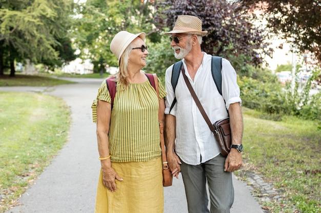 Händchenhalten des glücklichen paars und betrachten einander im park Kostenlose Fotos