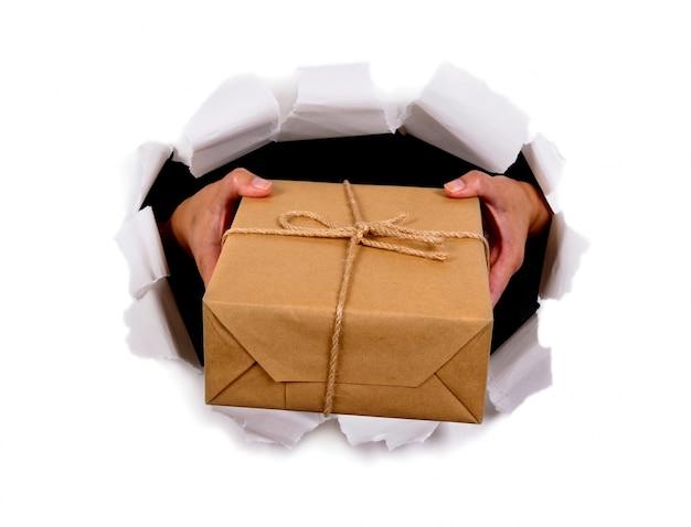 Hände bereitstellung von mail-paket durch zerrissene weißes papier hintergrund Kostenlose Fotos