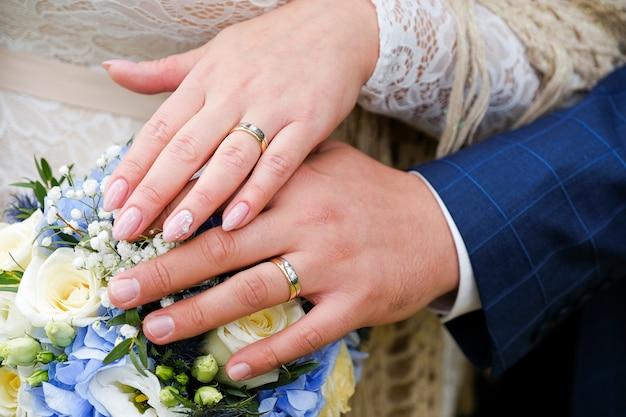 Hände der braut und des bräutigams auf dem hochzeitsblumenstrauß. goldhochzeitsringe auf den ringfingern der jungvermählten. Premium Fotos