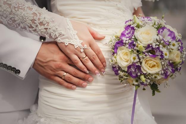 Hände der braut und des bräutigams mit hochzeitsblumenstrauß und -ringen Premium Fotos