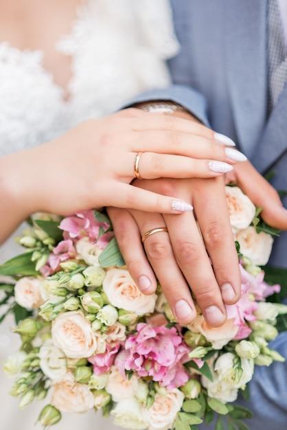 Hände der braut und des bräutigams schließen oben und tragen eheringe des weißgolds auf ihren händen Premium Fotos