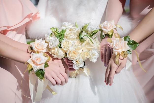Hände der braut und ihrer brautjungfern mit einem blumenstrauß Premium Fotos
