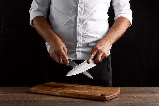 Hände der chefnahaufnahme schärft ein küchenmesser auf einem messer Premium Fotos