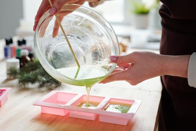 Hände der jungen frau, die flüssigseifenmasse mit grüner farbe von glaswaren in rosa silikonformen gießt Premium Fotos