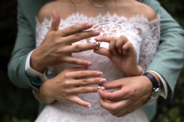 Hände der jungvermählten, die hochzeitsringe auf einander nahaufnahme setzen Premium Fotos