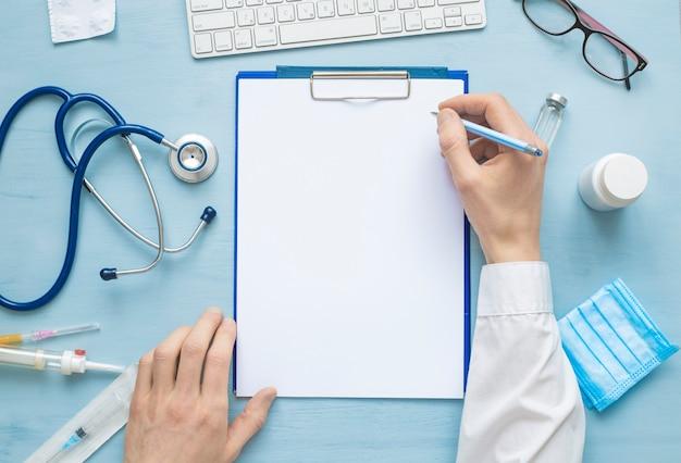 Hände des arztes, die ein rezept oder einen medizinischen bericht auf ein leeres blatt papier schreiben. Premium Fotos
