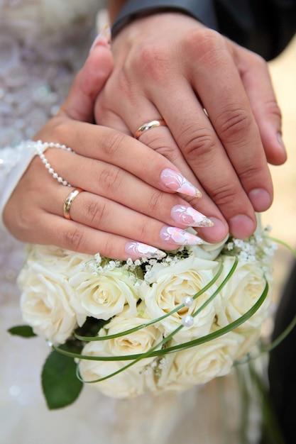 Hände des bräutigams und der braut mit eheringen halten einen hochzeitsblumenstrauß von den weißen rosen nah oben Premium Fotos