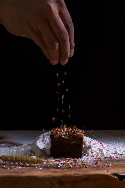 Hände des chefs, die süße schaumgummiringe mit puderzucker und mehlsieb besprühen Premium Fotos