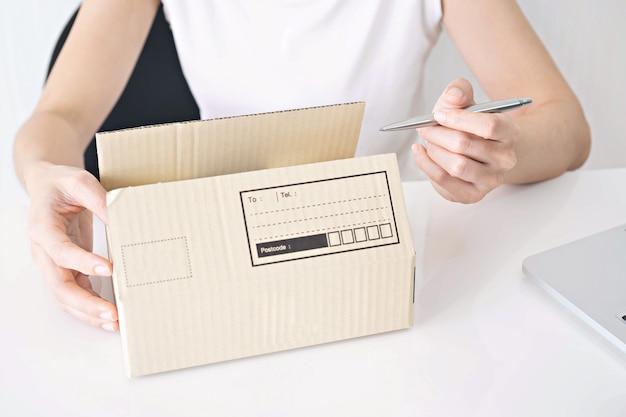 Hände des frauenschreibens auf pappschachtel bei tisch, konzept zu hause arbeitend Premium Fotos