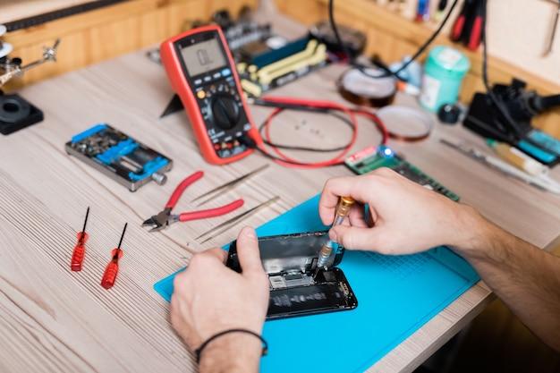 Hände des gadget-reparaturdienstmeisters mit einem schraubendreher, während winzige details des demontierten smartphones repariert werden Premium Fotos