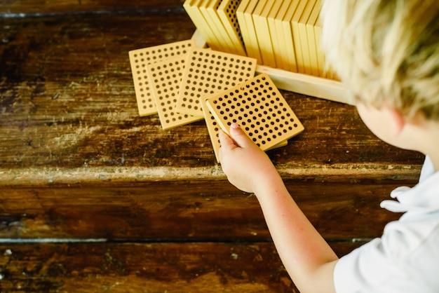 Hände des jungen zählende würfel auf hölzernem hintergrund in montessori-klassenzimmer manipulierend Premium Fotos