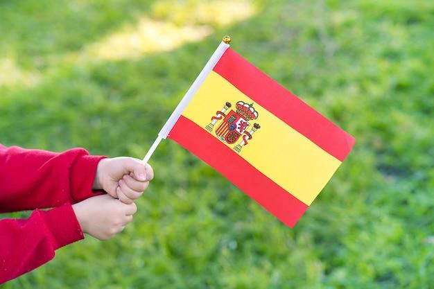 Hände des kleinen mädchens halten spanische flagge Premium Fotos