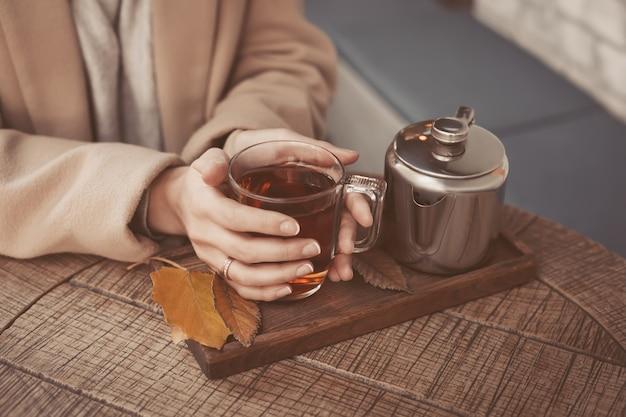 Hände des mädchens, die eine heiße tasse tee nahaufnahme anhalten Premium Fotos