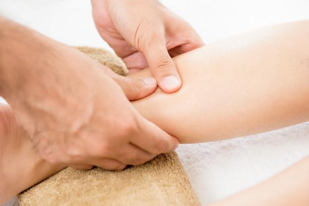 Hände des männlichen therapeuten einem frauenbein massage gebend Premium Fotos