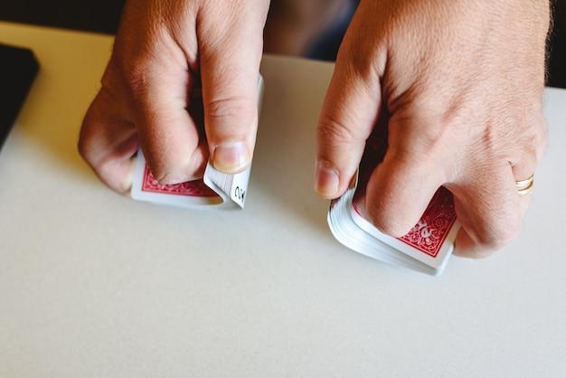 Hände des magiers, der ein deck von pokerkarten mischt, bevor er einen trick auf einer tabelle tut. Premium Fotos