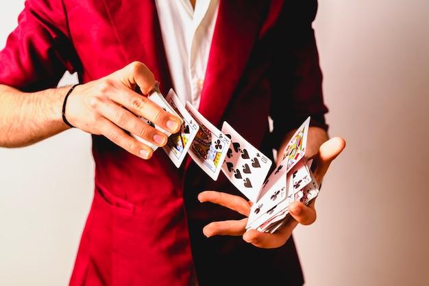 Hände des magiers tricks mit einem kartenstapel tuend. Premium Fotos